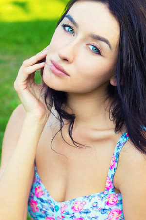 beautiful young sexy sweet girl with blue eyes with long black hair sitting in the Park on a clear summer day photo