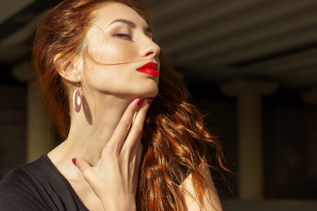 finger on lips: beautiful sexy girl with red hair with big red lips with makeup in the city on a Sunny summer day