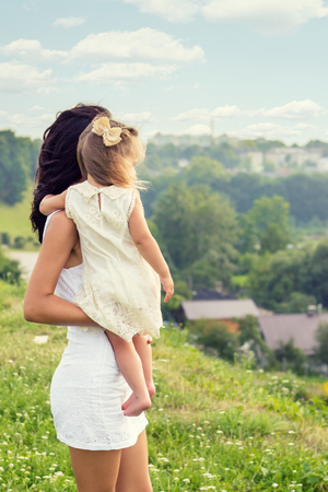 young mother with a small daughter in his hands standing on the edge of the cliff and looks into the distance over the city on a summer day photo