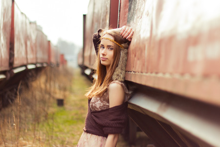 beautiful hippie girl with red hair and big lips stands near the old car near the railroad photo