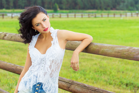 animal park: beautiful sexy brunette girl with red lips in the white shirt in denim shorts standing near the horse paddock