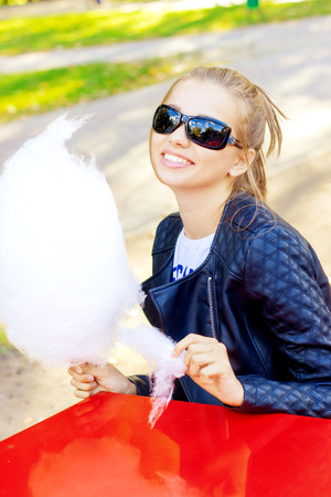 beautiful happy smiling girl in sunglasses eating cotton candy at a table in the Park on a Sunny day photo