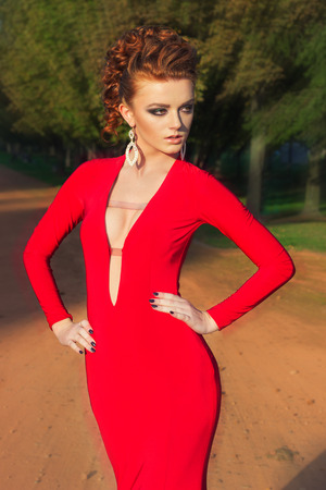 beautiful elegant girl with beautiful makeup and hair in a red evening dress in the Park photo