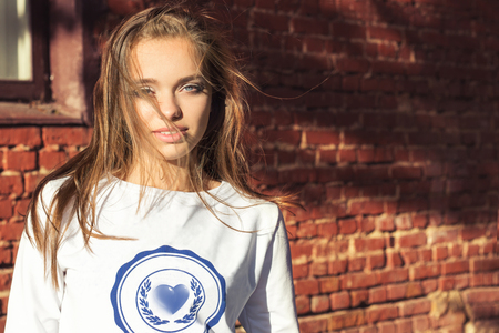 beautiful girl standing near the wall in a white jacket wind is blowing in your hair photo