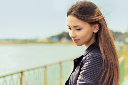 portrait of a beautiful elegant gentle graceful girl with dark hair standing by the lake photo
