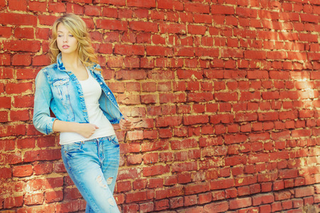 beautiful sexy blonde woman standing near a brick wall in a denim jacket and pants photo