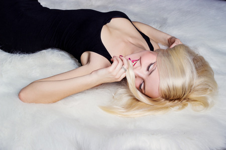 beautiful sexy happy women blonde with a smile lying on the white carpet in a black dress photo