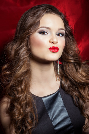 portrait of a beautiful sexy elegant girl brunette with long hair in evening dress with bright festive makeup and red lipstick in the Studio photo