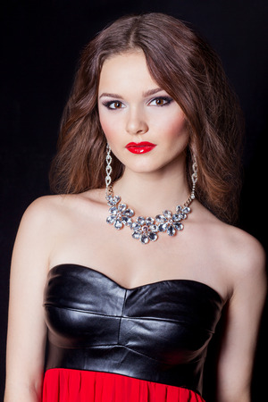 portrait of a beautiful sexy elegant girl in evening dress with a large necklace with a bright festive makeup Studio photo