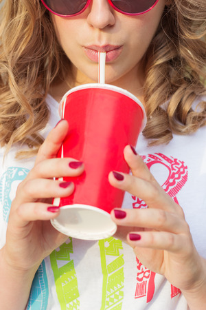beautiful young girl in sunglasses in the summer warm day drinking cola through a straw with red glass Stock Photo