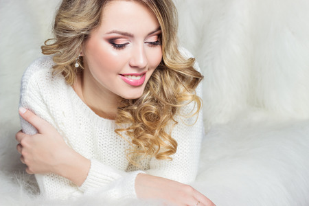 beautiful smiling happy girl with bright makeup lies on the bed with fur in white sweater photo