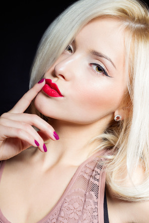portrait of a beautiful sexy women blonde with red lipstick and arrow in his eyes photo