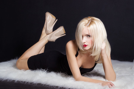 beautiful sexy elegant striking blonde woman with bright makeup red lips in a black dress lies on the white fur in the Studio on a black background Stock Photo