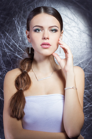 beautiful young girl with beautiful stylish expensive jewelry, necklace, earrings, bracelet, ring, filming in the Studio photo