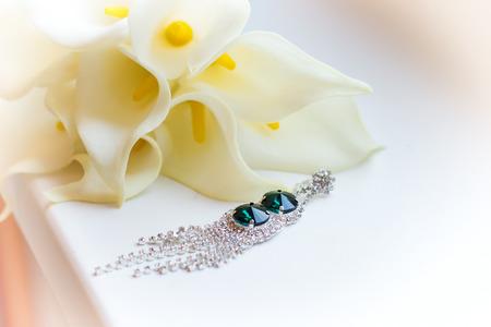 beautiful earrings on the windowsill near white flowers Kala wedding bouquet photo