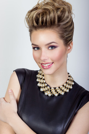 portrait of a beautiful happy sexy young woman smiling in a black evening dress with hair and make-up with expensive jewelry in Studio on white background