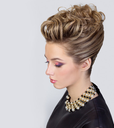 Beautiful young woman with evening make-up and salon hairdo . Smoky eyes. Complicated hairstyle for party photo