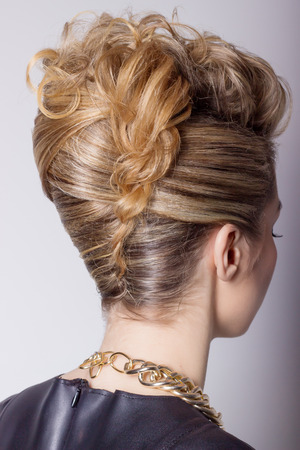 Beautiful woman with evening salon hairdo. Complicated hairstyle for party photo