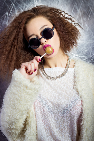 funny beautiful sexy girl in glasses and a white coat licks a candy bar, bright makeup, fashion photography Studio photo