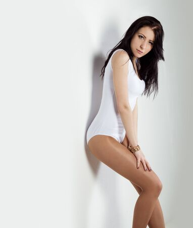 beautiful young girl with long dark hair in a white bodysuit stands near a white wall in the Studio photo