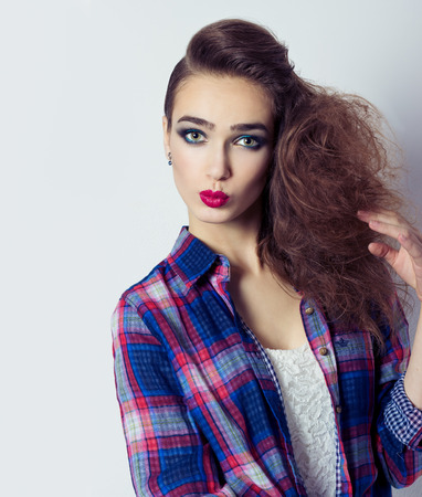 fashion photo of a beautiful girl with red lips, big eyes, bright makeup and stylish hair salon photo