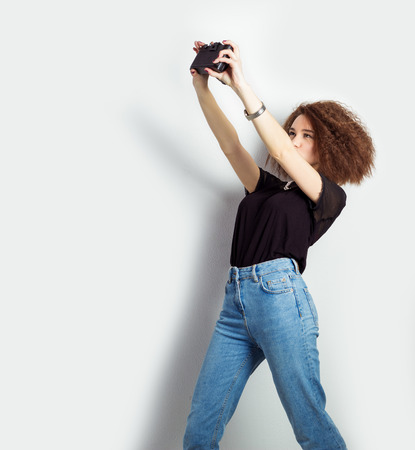 beautiful young girl hipster takes photos, shoots selfe, taking pictures of himself on camera in jeans and a black t-shirt in the Studio photo