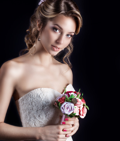 gentle portrait of happy smiling beautiful sexy girls in white wedding dress with a wedding bouquet in hand with beautiful hair and bright make-up, photography Studio Stock Photo