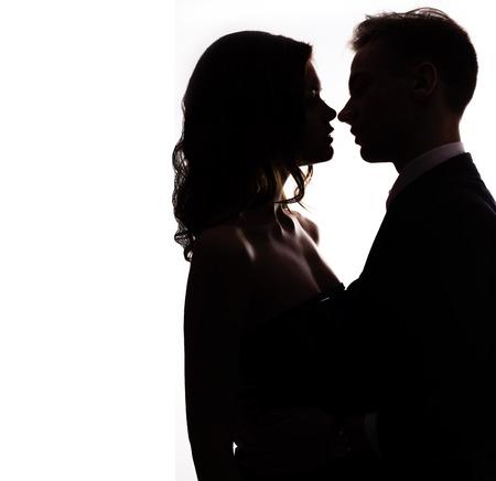 mujer sexy desnuda: silueta vlublennoj feliz pareja bes�ndose en un fondo blanco Foto de archivo