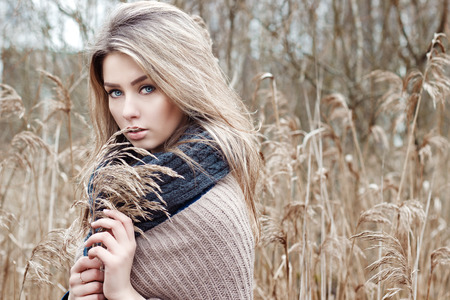 blue eyes girl: portrait of a beautiful girl with blue eyes in a grey jacket in the field among trees and tall dry grass, tinted in shades of gray
