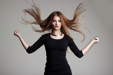 hair wind: beautiful sexy young woman in a black dress with bright makeup throws red hair Stock Photo