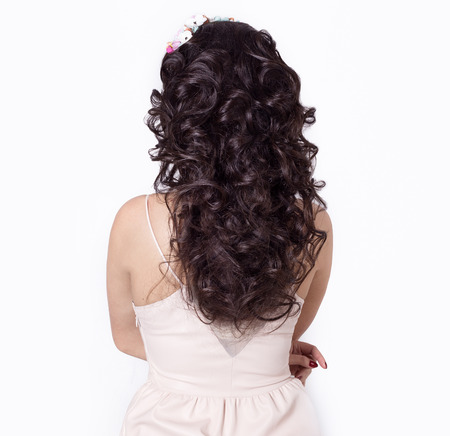 beautiful girl make her hair curls on long black hair decorated with a wreath of flowers photo