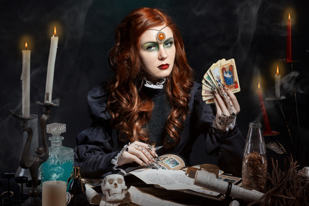 beautiful girl with long hair mode in the image of the witch with the Tarot cards in his hands black long false nails with bright makeup Stock Photo