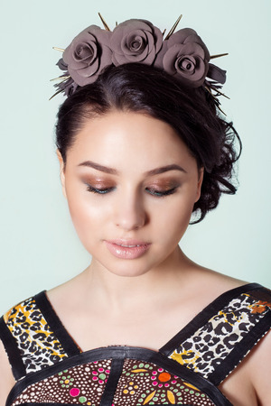 portrait of a girl brunete with hair beam with a delicate make up and a wreath in her hair from black roses with thorns rock photo