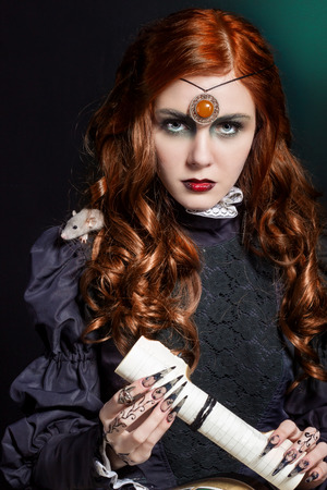 witchery: beautiful girl with long hair mode in the image of the witch with the mouse on his shoulder black long false nails with bright makeup