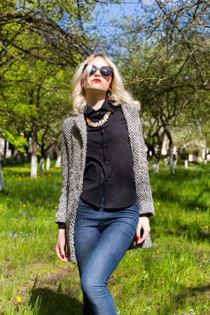 women hair: beautiful young happy blonde girl in coat jeans and sunglasses walking in the Park on a Sunny day