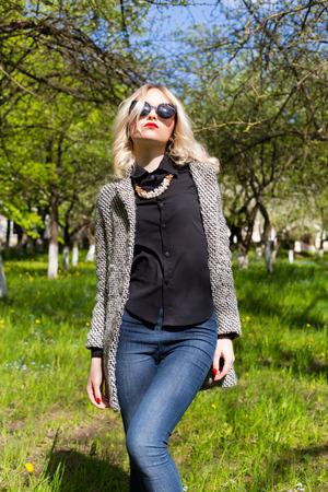 donne eleganti: bella ragazza bionda felice in jeans cappotto e occhiali da sole a piedi nel parco in un giorno soleggiato
