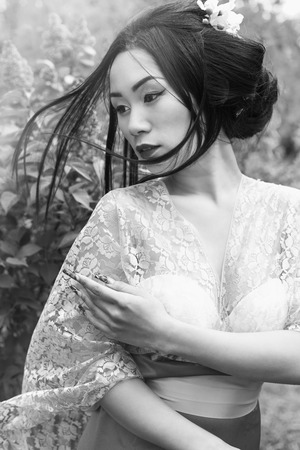 Chinese beautiful sexy girl in a kimono with a beautiful makeup with hair walking in a garden near blooming lilac bushes