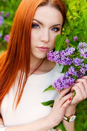 regime: beautiful sexy woman with fiery regime hair with eyes of a Fox in the garden with lilacs
