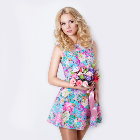 modest: beautiful sexy modest sweet tender girl with curly blond hair standing on white background with a bouquet of flowers of lavender in blue summer dress