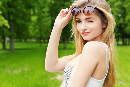 flirting women: Beautiful cute happy sexy girl with blond long hair in white Tshirt lifted sunglasses and winked Stock Photo