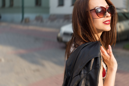 beautiful cute sexy happy smiling brunette girl in the big sunglasses walking around the city at sunset