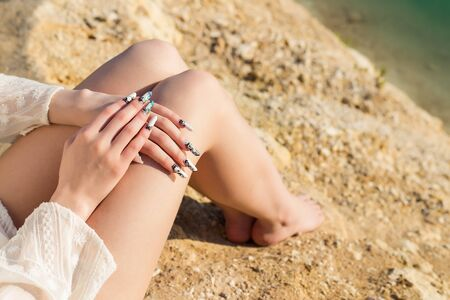 feet naked: beautiful long legs on the shore of the blue lake lie the hands on the knees with long acrylic nails