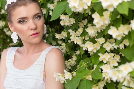 tree jasmine: beautiful sexy gentle pretty girl bride in a white dress, with delicate make-up and hair, with earrings made from flowers and crystals in a flowering tree Jasmine Stock Photo