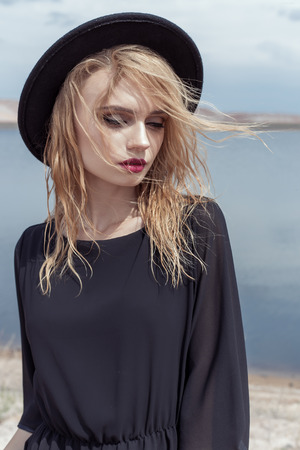 woman beach dress: fashion photo of young beautiful sexy girl with wet hair in a black hat and a black cotton dress with beautiful bright makeup, model proportionally