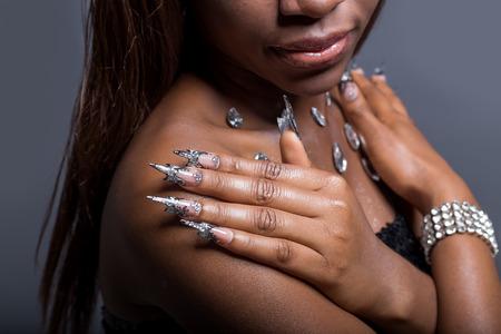modelos negras: Hermosa mano de la niña con la piel oscura en los hombros de injerto de uñas de acrílico con el clavo fotmoy inusual Foto de archivo