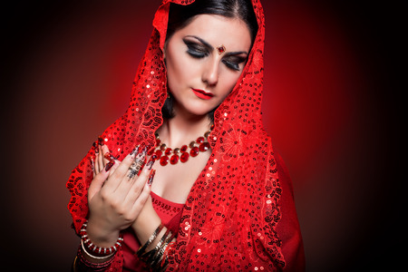 asian bride: beautiful girl in the image of Indian woman in a red sari with beautiful patch acrylic nails in oriental style in the studio