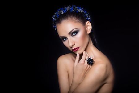 bared: expensive jewelry wreath earrings and ring on a beautiful sexy nude elegant brunette girl with bared shoulders with bright evening make-up