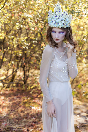 sexy elf: beautiful lovely gentle graceful fairy fairy in a flower crown and light dress walks through the woods on a sunny day early Stock Photo