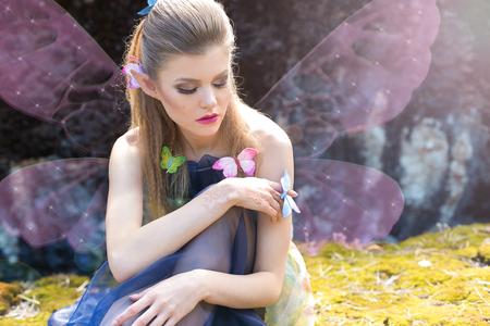 bruja sexy: hermosa mariposa elfo niña suave lindo sexy se sienta en un claro en el bosque en la luz del sol con las mariposas en su cabello y el brazo con maquillaje brillante Foto de archivo