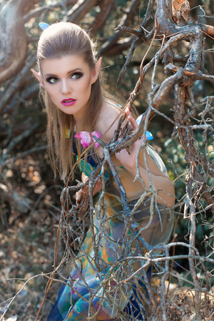 beautiful gentle sweet girl in the fairy tale character in the role of wood elf walking through the forest with butterflies in her hair and on the hand in a long dress with bright makeup and long ears